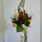 Les giroflées blanches, tulipes jaunes et lilium rouge composent un bouquet opulent sur une très haute flûte en verre.