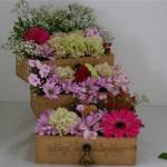Avec des fleurs variées, le thème secrets de tiroirs est composé dans des boîtes en bois.