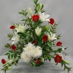Liliums blancs et renoncules rouges composent un opulent bouquet .