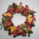 Brins d'eucalyptus stabilisés et baies rouges sont piqués dans une couronne en mousse florale.