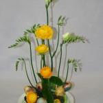 Renoncules jaunes et freesias complètent un groupe d'oeufs multicolores.