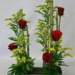 Des roses rouges sont associées aux solidagos et aux feuilles de xanadou.