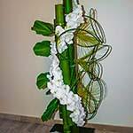 Une guirlande, composée en fleurons de phalaenopsis, grimpe le long des bambous.
