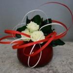 Sur le vase boule rouge, les rubans de bois rouges et blancs forment des méandres.