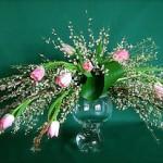 Explosion de genêts odorants et tulipes roses sur coupe en verre.