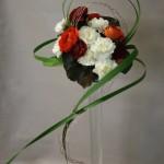 Bouquet rond d'oeillets  et renoncules sur haute flûte.