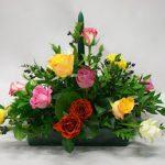 Centre de table avec bougie et roses multicolores.