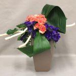 Oeillets et statice violet sont accompagnés de deux grandes feuilles d'Aspidistra.