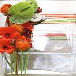 Harmonie de orange et vert, fils, fleurs et gros boutons en bois dans une coupe en verre.