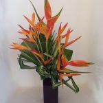 Végétaux exotiques en asymétrie : héliconias, feuilles de pandanus et tressage de feuilles.