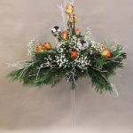 Des roses aux couleurs chaudes accompagnent les branches de myrtillier blanchies .